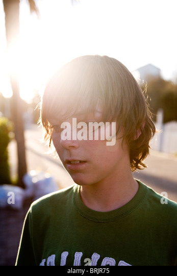 A teen boy is staring with the sun shining behind him. - Stock-Bilder