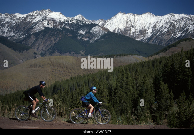 Colorado The West Rocky Mountain State Vail snow capped Gore Range bikers near Mid Vale ski lift station - Stock Image
