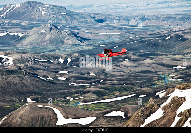 Aerial view, a red single-engine lightweight airplane flying over the volcanoes, Highlands of Iceland, Iceland, - Stock Image