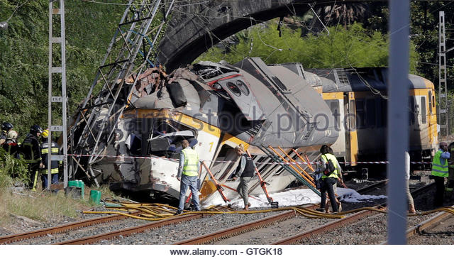 Rescue workers inspect a train that derailed in Galicia in north-western Spain, close to the town of O Porrino, - Stock-Bilder