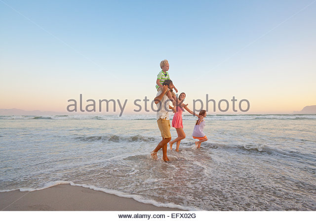 Happy family walking through waves, holding hands and son having piggy-back, on sunny beach - Stock Image