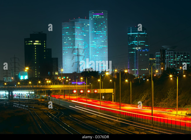 Night view of Tel Aviv city downtown, illuminated Azrieli towers and light traces on Ayalon highway. - Stock Image