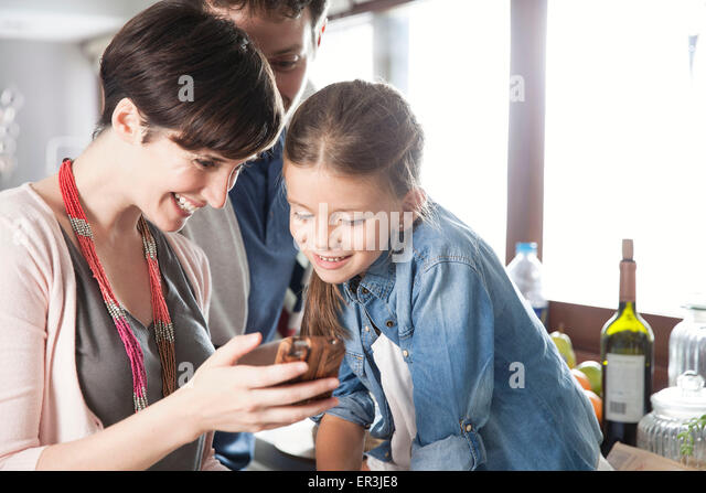 Family looking at smartphone together - Stock-Bilder