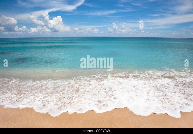 Empty beach with white wave spray - Stock Image