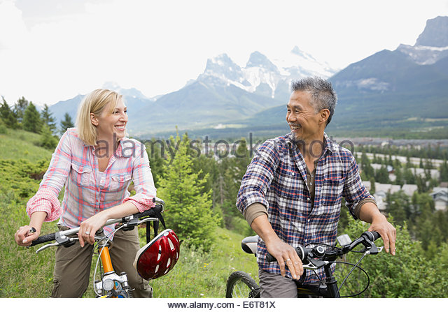 Couple standing with mountain bikes on hillside - Stock Image