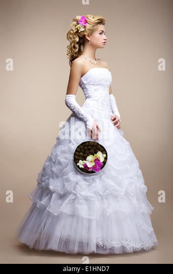 Wedding Style. Bride wearing White Dress and Gloves. Trendy Bouquet of Flowers - Stock Image