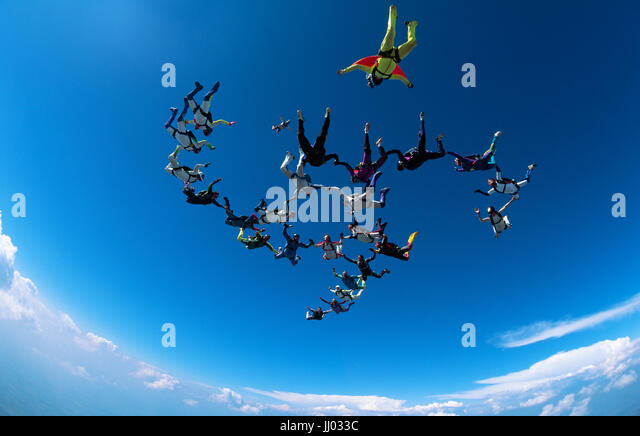 Skydivers tumble through the air after exiting an Mi26 helicopter - Stock Image