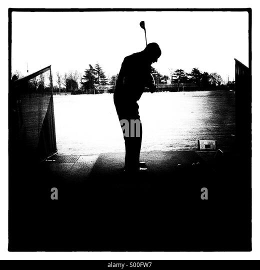 Golfer hitting golf ball with driver at driving range - Stock Image