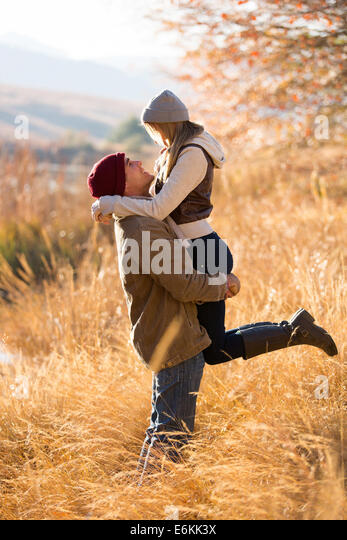 playful young man picking up his girlfriend by the lake in fall - Stock Image