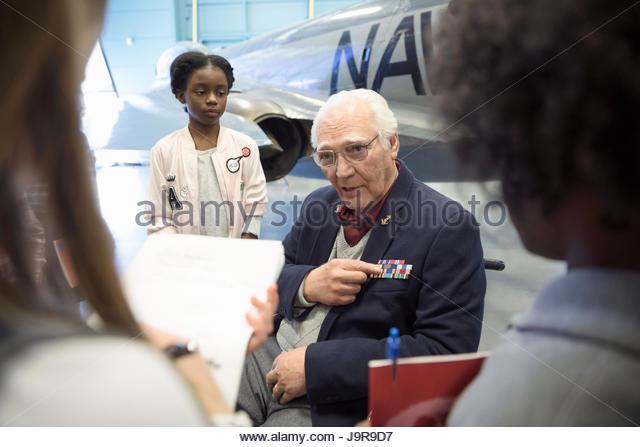 War veteran explaining stripes to students on field trip in Naval war museum - Stock-Bilder