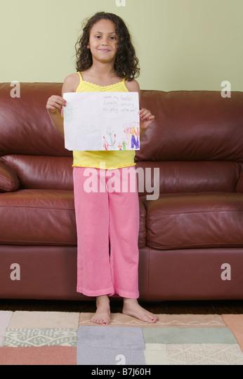 Mulatto girl showing off her artwork (6 years). - Stock Image