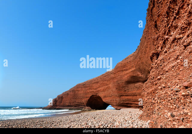 Natural sea-worn rock archways against clear blue sky at Legzira beach, Morocco. - Stock Image