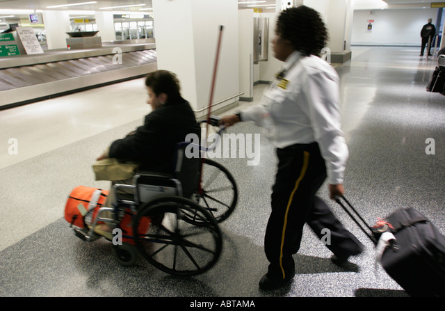 New Jersey Newark Airport Black female attendant pushes wheelchair pulls luggage disabled woman baggage claim - Stock Image