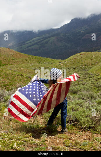Girl with American flag in field - Stock Image