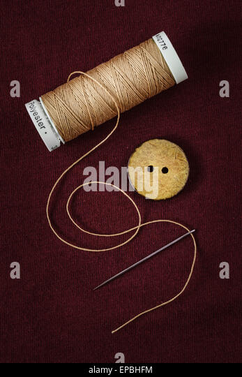 Close up of thread, single button and needle - Stock Image