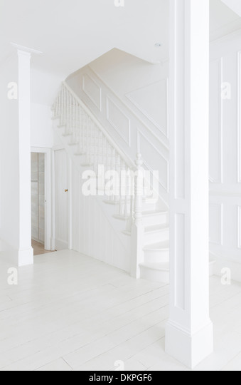Staircase in white foyer - Stock Image