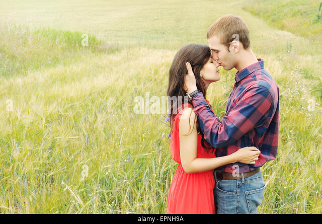 stunning sensual outdoor portrait of young stylish fashion attractive couple in love kissing in summer field - Stock-Bilder