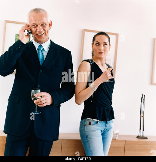 cell phone color image communication dressed up man party several suit tie wine woman - Stock-Bilder
