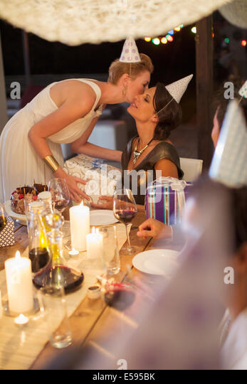 Woman giving gift at birthday party - Stock-Bilder