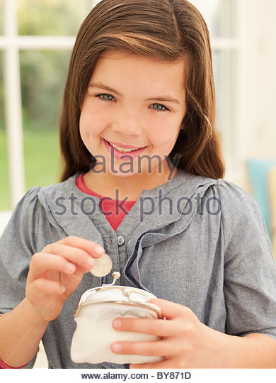 Smiling girl putting money into coin purse - Stock Image