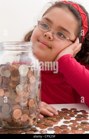 Young girl with jar full of coins - Stock Image