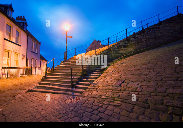 A traditional street light illuminates the 199 steps leading down towards the old town of Whitby. - Stock-Bilder