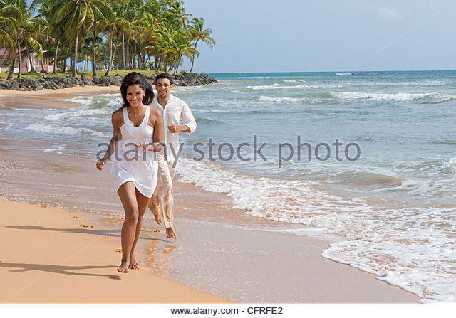 Hispanic couple running along the shore of LaPared Beach, Luquillo, Puerto Rico, United States of America, Central - Stock Image