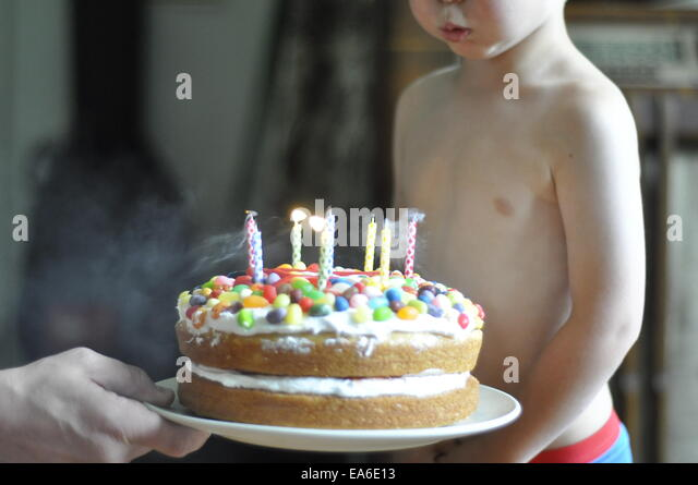 Boy blowing out candles on birthday cake - Stock Image