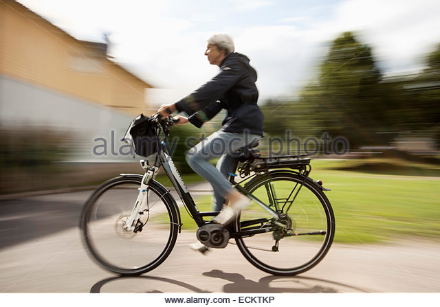 Blurred motion of senior woman cycling on street - Stock Image