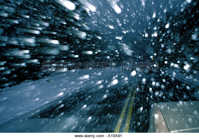 Driving into snowstorm on Mount Lemmon Highway with  large snow flakes zooming by. - Stock Image