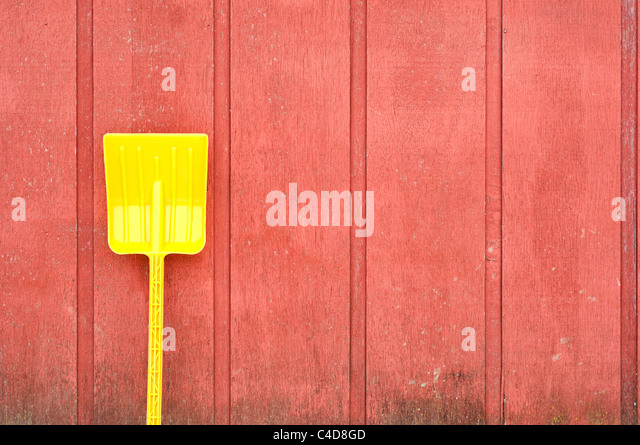 A plastic yellow toy shovel leans against a red wooden barn wall - Stock-Bilder