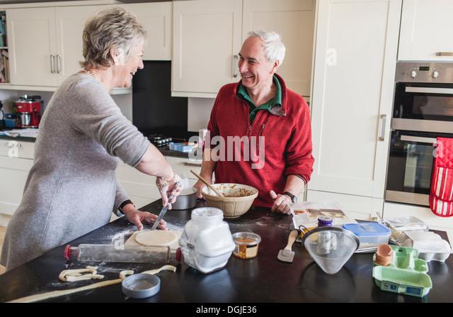 Senior couple preparing pastry - Stock Image