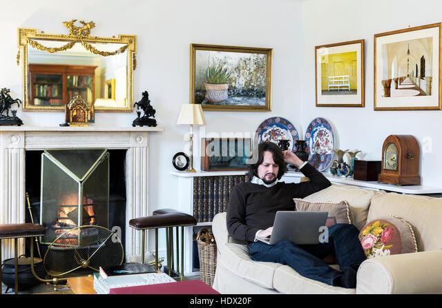 Caucasian man sitting on sofa using laptop - Stock Image