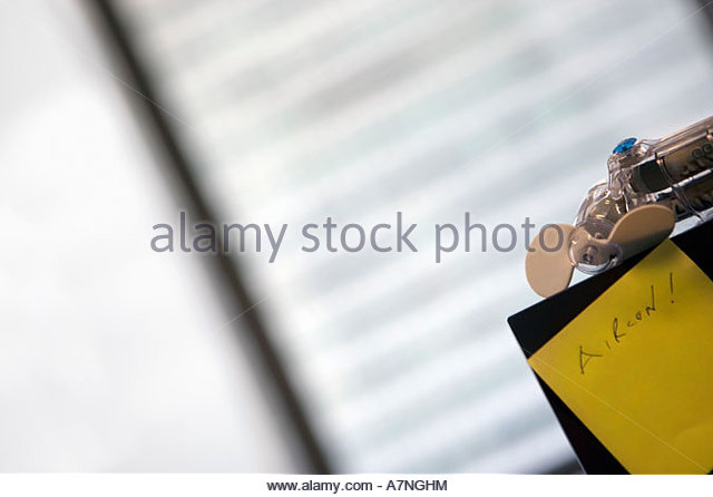 Focus on small fan and yellow post it note with the word Aircon close up tilt - Stock Image