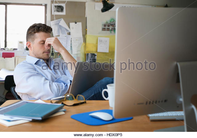 Frustrated Caucasian businessman with laptop in office - Stock Image