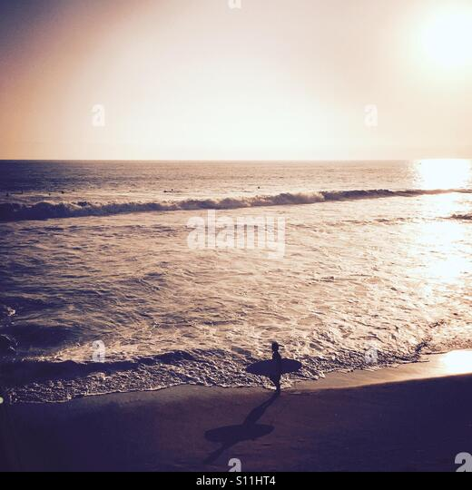 A Surfer walking down the beach checking out the waves. Manhattan Beach, California, USA. - Stock Image