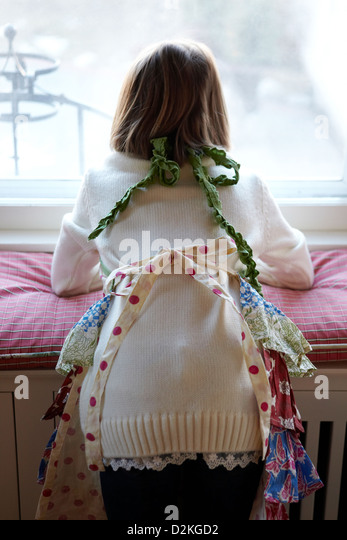 Child wearing apron looking out window from behind - Stock Image