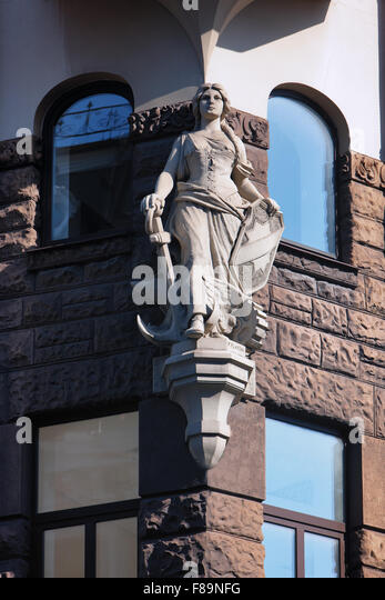 Sculpture of a woman with an anchor and a shield in the corner of the building facade with windows in the old center - Stock Image
