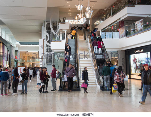 Inside view of Yorkdale Shopping Center in Toronto brimming with people. Various brand shops and escalator visible - Stock Image