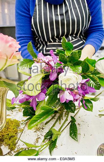 Floral designer preparing bunch of flowers in studio - Stock Image