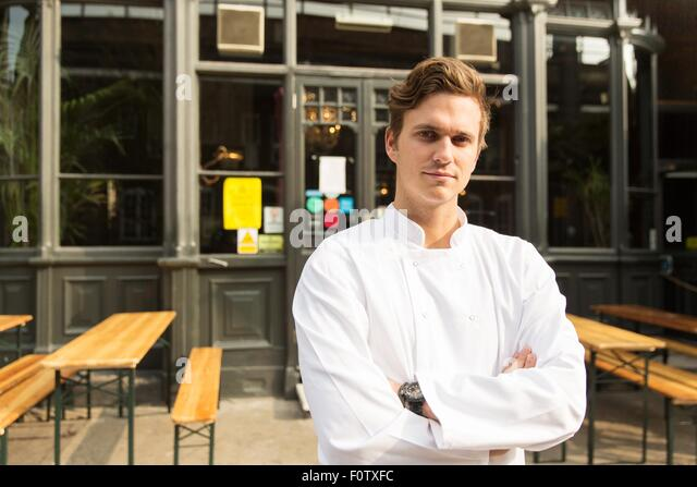 Young chef standing outside of work, arms folded - Stock Image