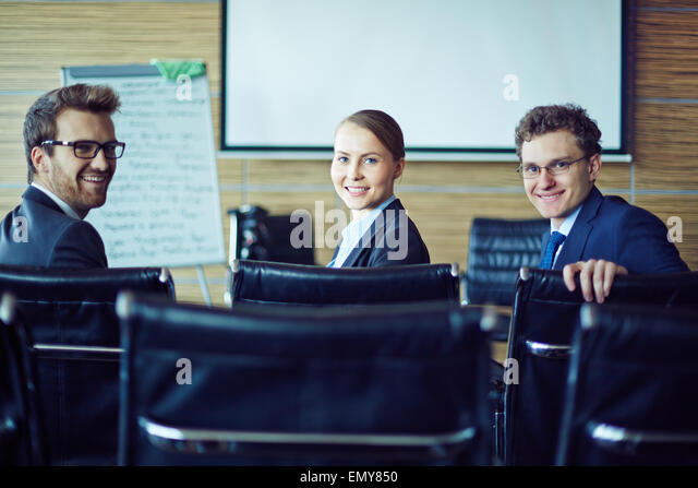 Happy co-workers looking at camera in conference hall - Stock Image