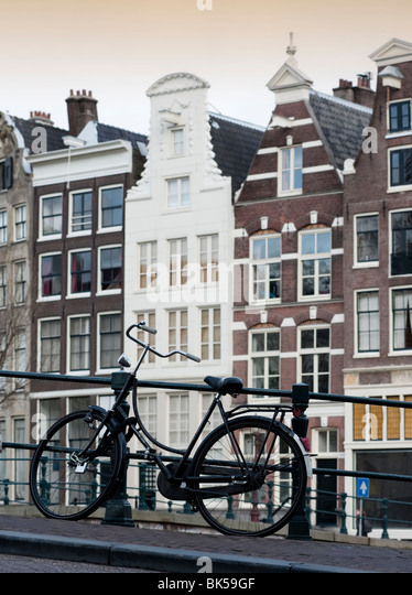 Bicycle parked on bridge above canal in central Amsterdam Netherlands - Stock Image