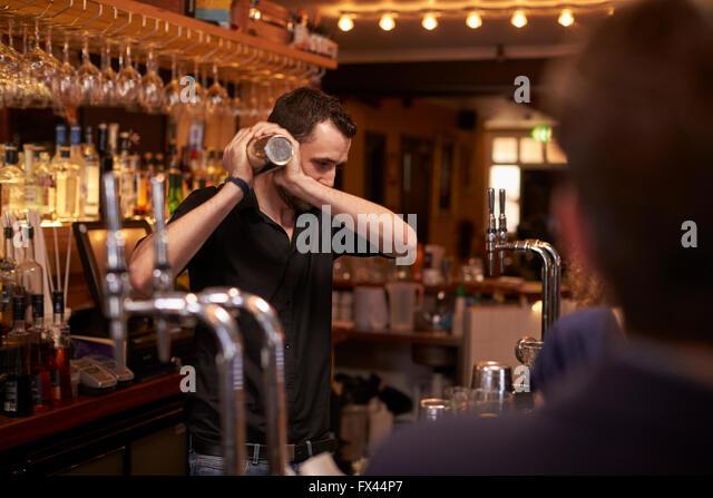 Barman Making Cocktail In Bar Using Shaker - Stock Image