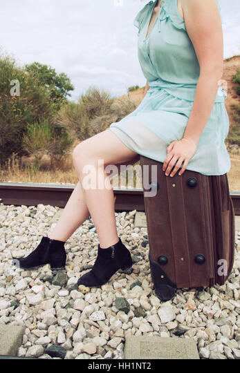 Woman sitting in a vintage suitcase - Stock Image