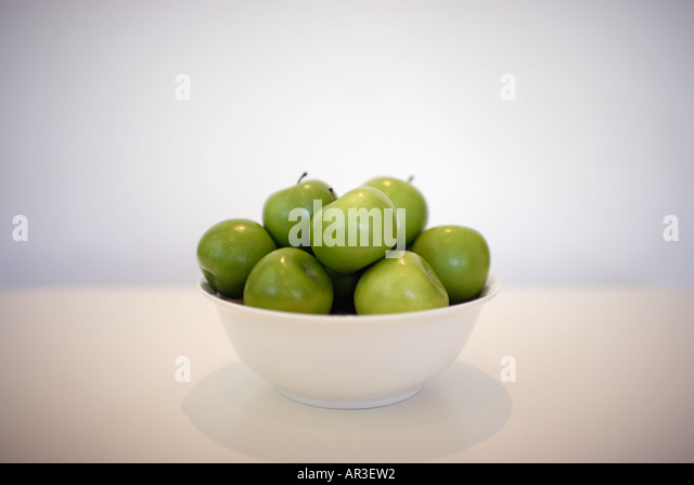 Bowl full of green apples on a white table - Stock Image