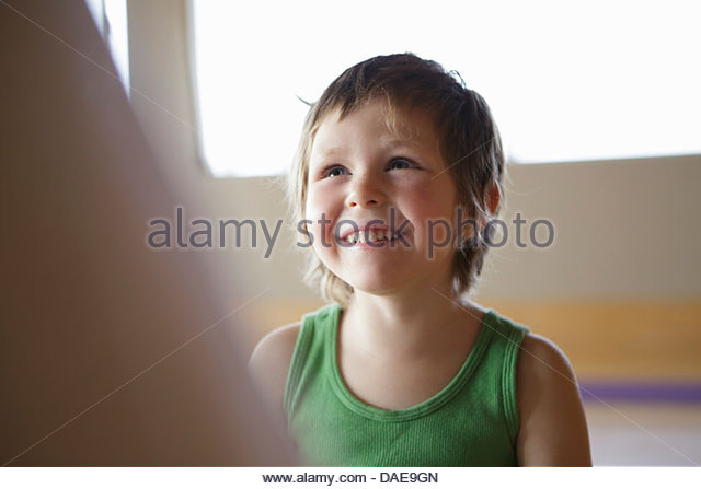 Candid portrait of smiling young girl in green vest - Stock Image