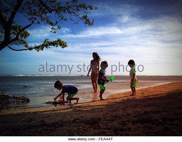 Family On Beach Against Cloudy Sky - Stock-Bilder