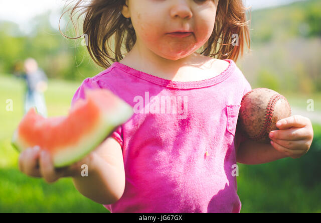 A young girl eats a watermelon and holds a baseball in summer - Stock Image