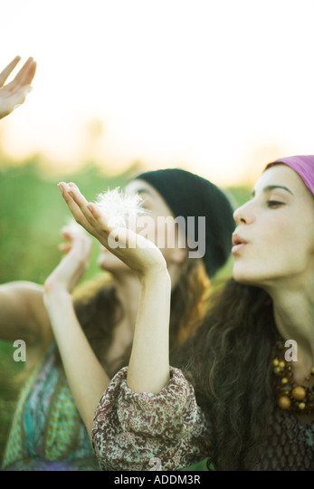 Young hippie women blowing dandelion seeds - Stock-Bilder